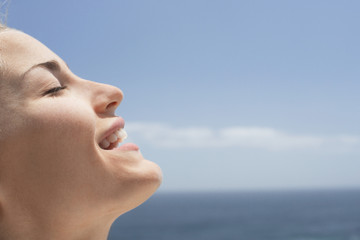 Young woman with eyes closed on beach, close-up