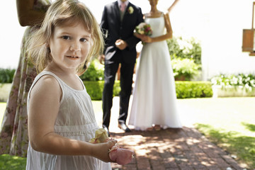 Young girl holding flower petals, bride and groom standing in background