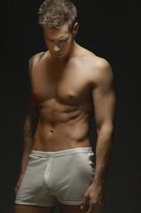 man wearing underwear, on black background, portrait