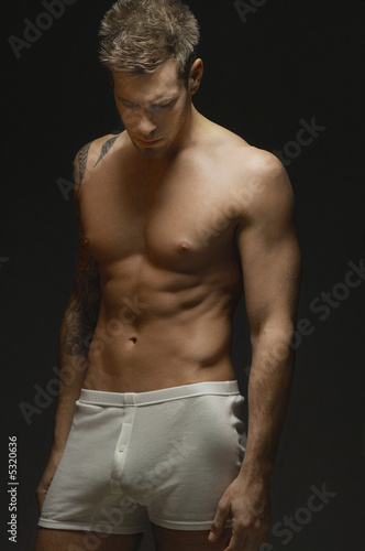 man wearing underwear, on black background, portrait