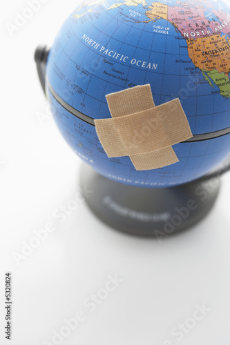 Two pieces of sticking plaster on globe, close-up
