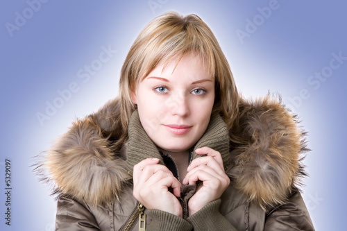 young girl in a jacket with a fur collar on a light blue backgro