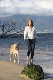 Woman walking dog on leash on Maui, Hawaii beach. poster