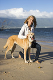 Woman with dog on leash on Maui, Hawaii beach. poster