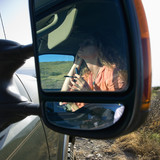 Reflection in vehicle side mirror of a woman applying mascara. poster