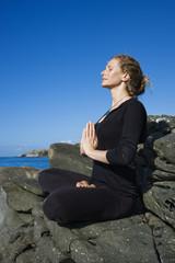 Woman practicing yoga on rocky coast of Maui, Hawaii.