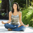 Woman sitting in lotus position practicing yoga.