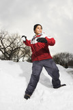 Boy standing in snow throwing snowball. poster