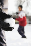 Boy holding snowball ready to throw at boy in background. poster
