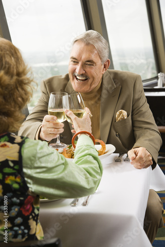 poster of Mature couple dining in restaurant with rooftop view of city.