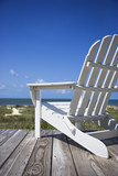 Empty white adirondack chair on wooden deck facing beach.
