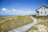 Beachfront house with wooden walkway. poster