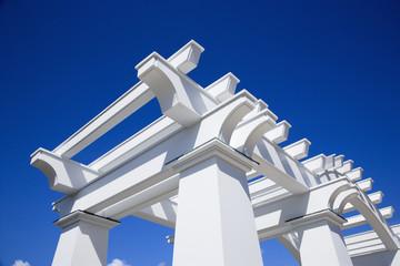 Detail of white arbor against blue sky.