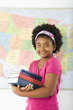 Girl standing in front of USA map holding books smiling.