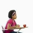 Side view of African American girl sitting in school desk.