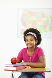 Girl sitting in school desk smiling at viewer. poster