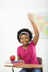 Girl sitting in school desk raising hand and smiling at viewer.