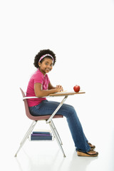 Side view of girl sitting in school desk smiling at viewer.