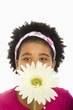 Girl holding large daisy over face and looking at viewer.