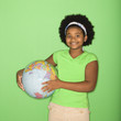 girl holding globe at hip and smiling at viewer.
