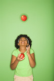 African American girl juggling apples. poster