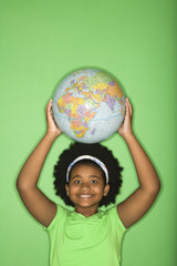 Girl holding globe on top of head and smiling at viewer.