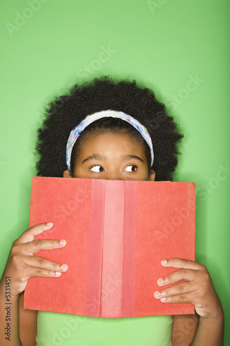 girl with book held up to face looking suspiciously to the side.