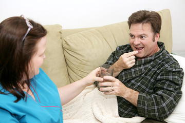 Patient taking medication from his home health care nurse.