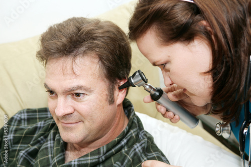 Home health nurse using an otoscope