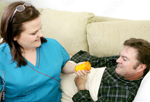 Home health nurse gives her patient his medicine.