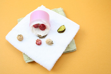 Spa essentials (cream, white towel and pink flowers) i