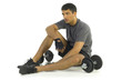 Young man resting after exercising with dumbbells