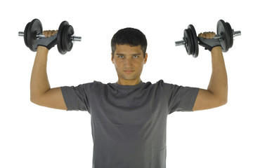 Young man exercising arms muscles with dumbbells