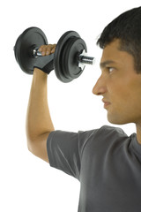 Young man exercising arm muscles with dumbbell