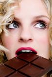 Fototapety weibliches Gesicht mit blick nach oben beim essen von Schokolade