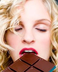 Blonde Frau geschlossenen Augen Schokolade auf Zunge zergehen