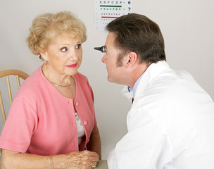 Optician looking into a senior woman's eyes