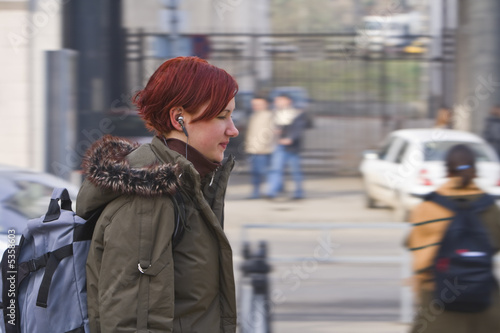 Redhead girl listening to music while walking in a city.