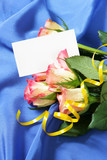 Roses over blue silk background with blank visiting card poster