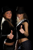 two girls in black hats with thumbs up