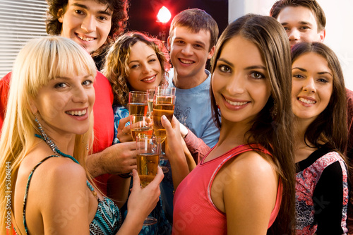 Portrait of seven friends holding glasses of champagne