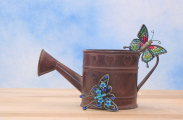 Metal Watering Can on Blue Sky Background With Betterflies
