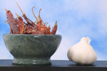 Peppers and Garlic on Black Table With Blue Sky Background