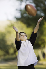 Young boy with arms stretched out to catch a football