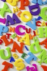 Composition of colorful plastic toy letters over white