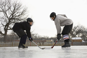 Two ice hockey player boys in uniform facing off on ice.