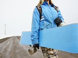 Woman carrying snowboard. poster