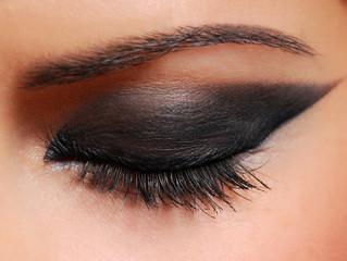 Long woman eyelashes brushing black mascara.
