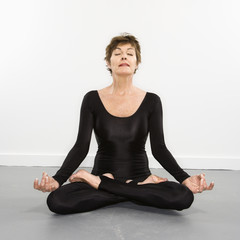 Woman in spandex bodysuit sitting in meditation lotus pose.