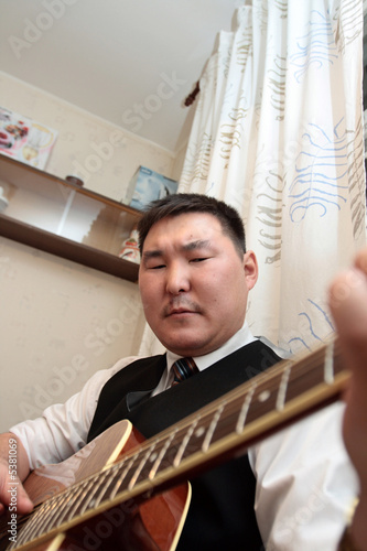 The man playing the guitar at home